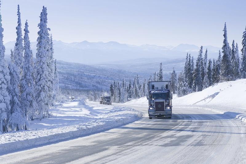 Big Rig Semi-Trucks driving up a steep grade on an Arctic Winter Highway in Alaska